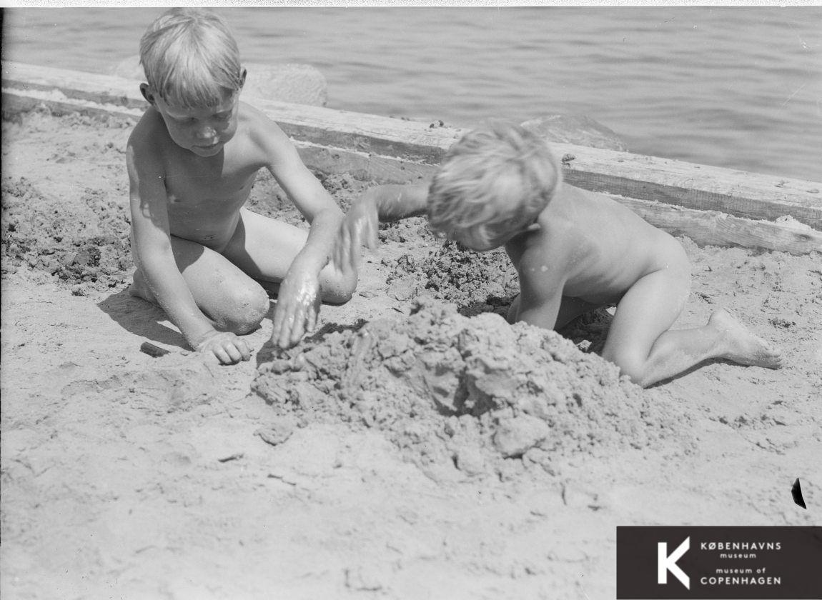 To små drenge bygger sandslot  i vandkanten: strandområde, børnegruppe