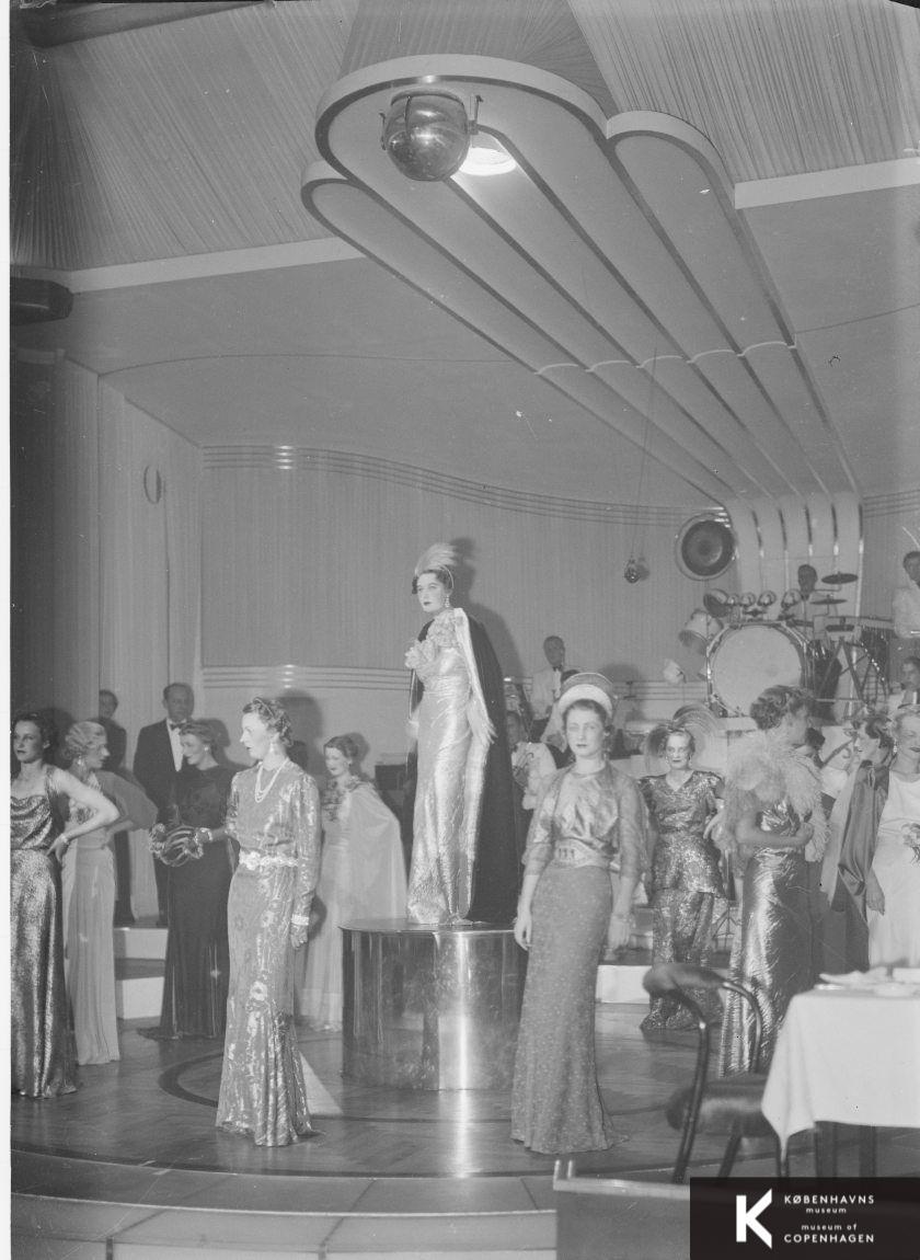 9176696fe25 Modeopvisning af elegante kjoler på en scene med et orkester i baggrunden